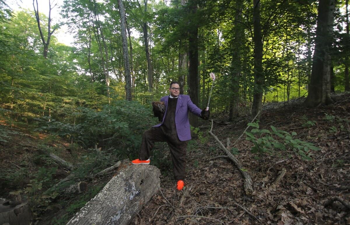 Jay Baer im Bärenkostüm inmitten eines dichten Waldes. Er hat den Fuß auf einem Baumstamm gestellt und fotografiert sich mit einem Selfie-Stick.